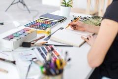 Vista di angolo del primo piano di un progetto femminile del disegno del pittore allo sketchbook facendo uso della matita Artista fotografie stock libere da diritti