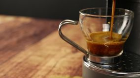 Vista di angolo della fine su del caffè italiano del caffè espresso La mano di una donna riposa la tazza di vetro sotto i getti d archivi video