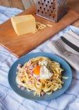 Vista di angolo di pasta con l'uovo, il prosciutto, il formaggio e le erbe Cena Mediterranea con la coltelleria sull'asciugamano  fotografie stock libere da diritti