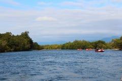 Vista di bello fiume della montagna con i turisti sulle zattere su acqua immagini stock