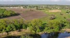 Vista di bello villaggio con i campi neri, i prati verdi e un piccolo lago Fotografia Stock Libera da Diritti