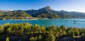 Vista di estate del lago Serre-Poncon con Savines-le-bacca ed il grande picco di montagna di Morgon Alpi, Francia Immagini Stock