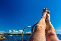 Vista di estate di vacanza - gambe contro acqua e cielo blu Fotografia Stock Libera da Diritti