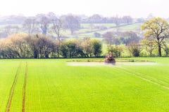 Vista di giorno soleggiato dei trattori che spruzzano campo britannico Fotografia Stock