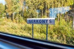 Vista di giorno soleggiato della targhetta della città di Gerkonys attraverso la finestra del treno che viaggia dai visaginas a V fotografia stock