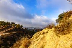 Vista di Hillside delle tracce di escursione e della città distante all'alba fotografie stock libere da diritti
