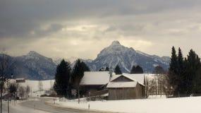 Vista di inverno delle montagne delle alpi dal villaggio qui sotto Fotografie Stock Libere da Diritti