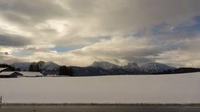Vista di inverno delle montagne delle alpi dalla strada qui sotto Fotografia Stock