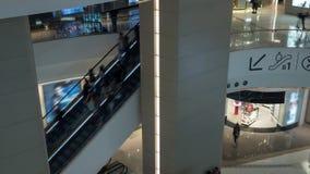 Vista di lasso di tempo di traffico pedonale della gente sulla scala mobile nel grande centro commerciale multilivelli video d archivio