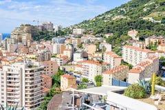 Vista di luce del giorno alle costruzioni alte della città, alberi verdi sulle montagne a Fotografie Stock Libere da Diritti