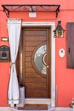 Vista di luce del giorno per alloggiare entrata con la porta di legno fotografie stock libere da diritti