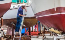 Vista di lungomare di Ginevra - barca della riparazione dell'uomo Fotografie Stock Libere da Diritti