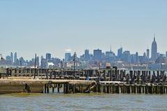Vista di Manhattan attraverso il fiume Hudson con il pilastro di legno in priorità alta Fotografia Stock
