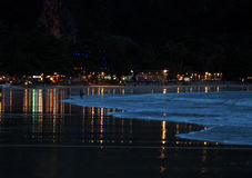 Vista di notte ad una riva dell'oceano con le luci Fotografia Stock
