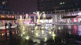 Vista di notte dei giochi variopinti dell'acqua delle fontane nel quadrato di Gael Aulenti a Milano l'ultimo giorno archivi video