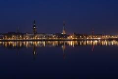 Vista di notte del centro di Riga con la riflessione in Daugava Fotografia Stock