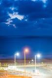 Vista di notte del mare con tre pali elettrici variopinti Immagini Stock
