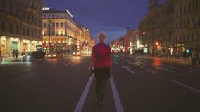 Vista di notte di una strada e di un backview della ragazza che vanno al centro della strada video d archivio