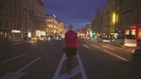 Vista di notte di una strada e di un backview della ragazza che vanno al centro della strada archivi video