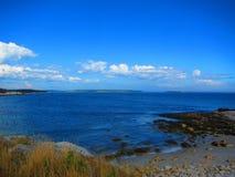 Vista di oceano da una riva rocciosa con una piccola spiaggia Fotografie Stock
