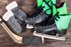 Vista di OOverhead degli accessori dei pattini da ghiaccio dell'hockey disposti su vecchio ru Fotografia Stock Libera da Diritti