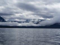 Vista di panorama delle montagne della neve con le nuvole/nebbia lungo la costa Fotografie Stock Libere da Diritti
