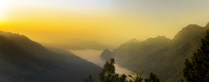 Vista di panorama di luce solare arancio sopra l'alta montagna e la nebbia Fotografia Stock Libera da Diritti