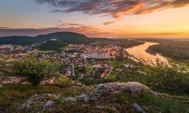 Vista di piccola città con il fiume dalla collina al tramonto Immagini Stock Libere da Diritti