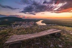 Vista di piccola città con il fiume dalla collina al tramonto Fotografie Stock