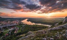 Vista di piccola città con il fiume dalla collina al tramonto Fotografia Stock Libera da Diritti