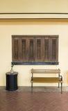 Vista di prospettiva della sedia di legno lunga di stile d'annata e di grande vaso da fiori nero sul marciapiede del mattone, pav Fotografie Stock