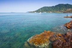Vista di vista sul mare con roccia dietro il fondo della montagna immagine stock