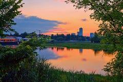Vista di tramonto con la città vicino al lago Fotografie Stock Libere da Diritti