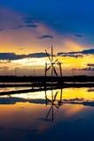 Vista di tramonto dell'azienda agricola del sale e della ruota di vento Fotografia Stock