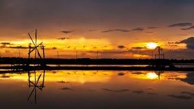 Vista di tramonto dell'azienda agricola del sale e della ruota di vento Immagini Stock Libere da Diritti