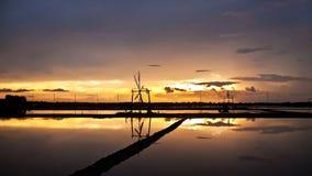 Vista di tramonto dell'azienda agricola del sale e della ruota di vento Fotografia Stock Libera da Diritti