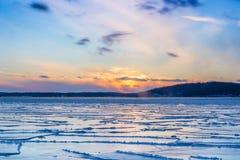Vista di tramonto e lago congelato Immagini Stock