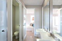 Vista di un bagno moderno con la toilette ed il modo alla camera da letto Immagine Stock