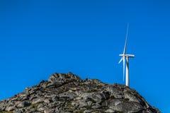 Vista di un generatore eolico sopra le montagne immagini stock libere da diritti