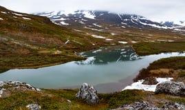 Vista di un lago della montagna che parzialmente riflette una montagna accampamento Immagini Stock Libere da Diritti
