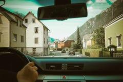 Vista di un traffico della via e delle case norvegesi bianche da ogni lato dall'interno del ` s dell'automobile Immagini Stock