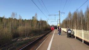 Vista di un treno elettrico rosso delle ferrovie russe che si avvicinano al binario nella periferia stock footage