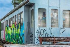 Vista di un vagone abbandonato con arte della via dei graffiti e la riflessione dei bambini sul vetro di finestre immagine stock