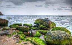 Vista di una baia rocciosa con cloudscape drammatico Immagine Stock Libera da Diritti