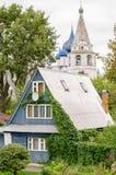 Vista di una casa di legno tradizionale ed il Cremlino di Suzdal'nei precedenti Immagine Stock