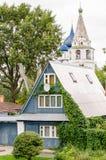 Vista di una casa di legno tradizionale ed il Cremlino di Suzdal'nei precedenti Immagine Stock Libera da Diritti