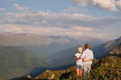 Vista di una coppia che guarda il tramonto su un prato e sulla montagna fotografia stock libera da diritti