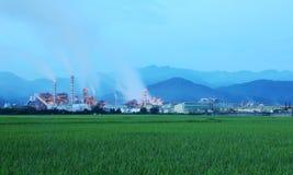 Vista di una fabbrica in mezzo ad un terreno coltivabile verde nella penombra di primo mattino fotografia stock libera da diritti