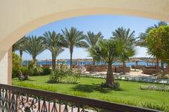 Vista di una spiaggia tropicale con i giardini Fotografie Stock Libere da Diritti