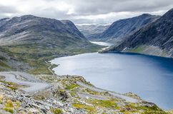 Vista di una valle del ghiacciaio e del lago dalla strada che conduce al punto di vista di Dalsnibba con le montagne dietro immagini stock